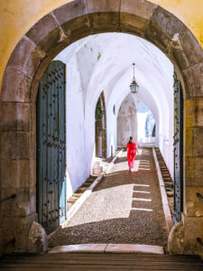 Girl in red dress walking down white tunnel