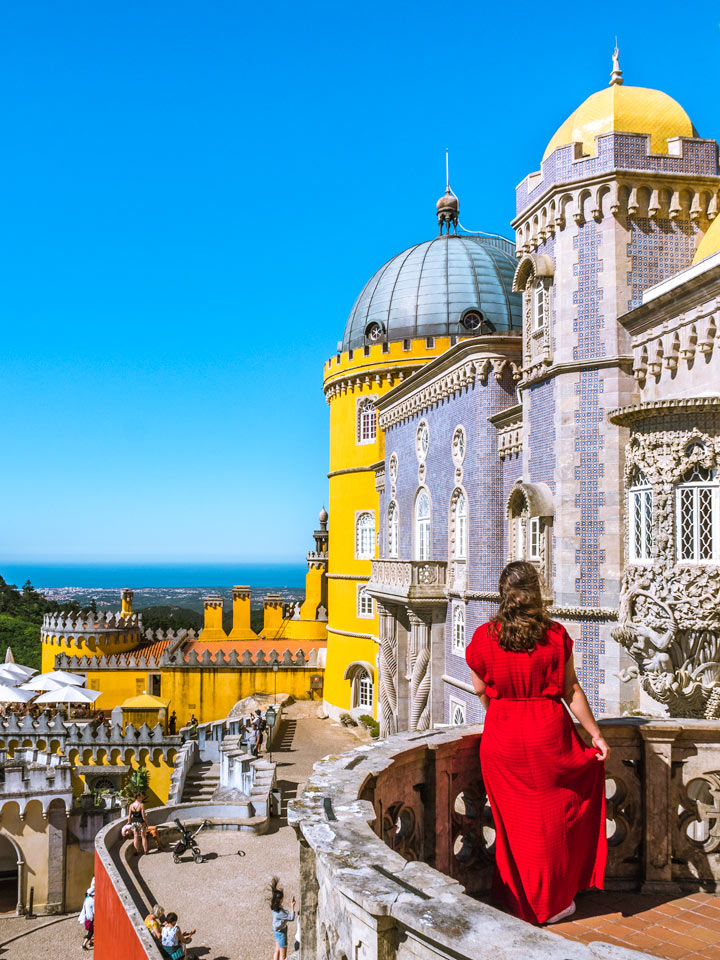 Girl in red dress on balcony overlooking Pena Palace and ocean