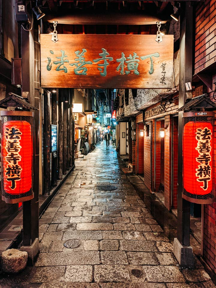 Osaka alley at night with red lanterns and stone path