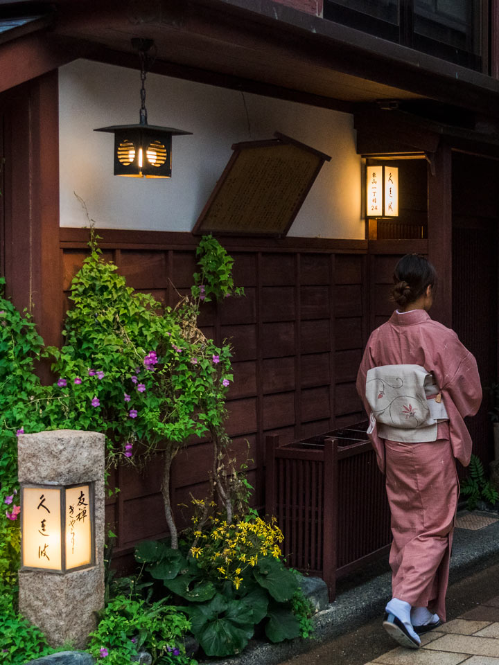 Woman in pink kimono walking in evening under lanterns
