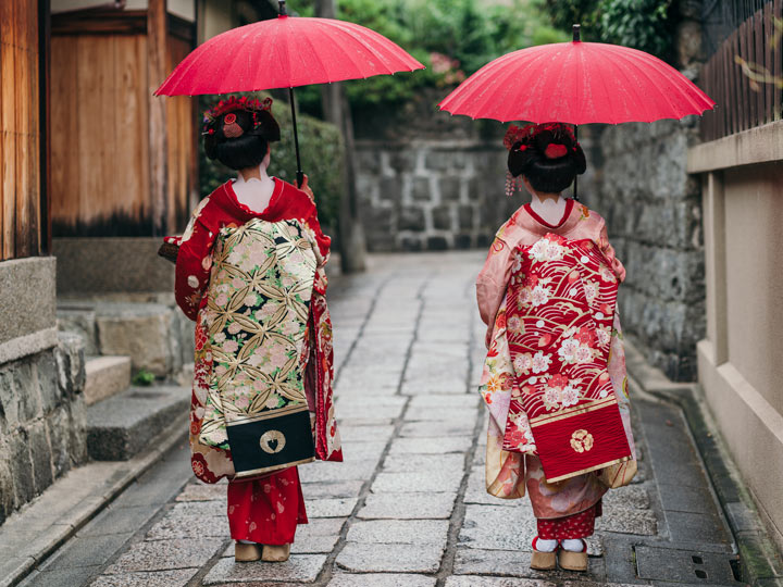 Two maikos in red kimonos and parasols spending 10 days in Japan