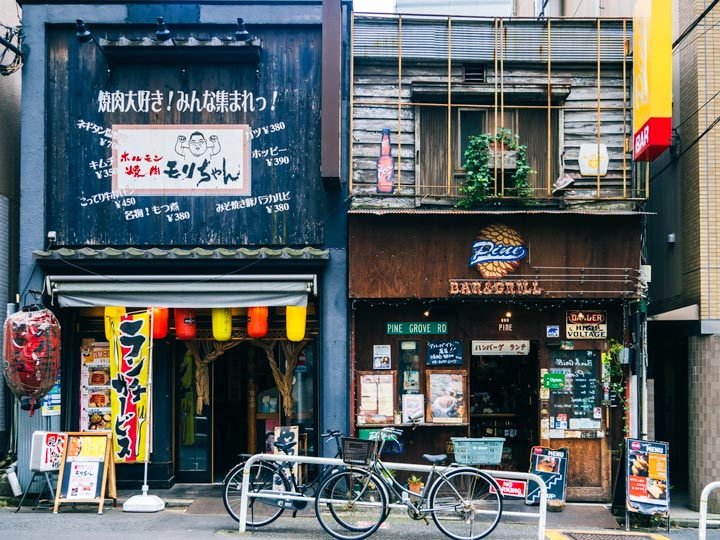 Blue and brown facades of old Tokyo cafes with bikes out front