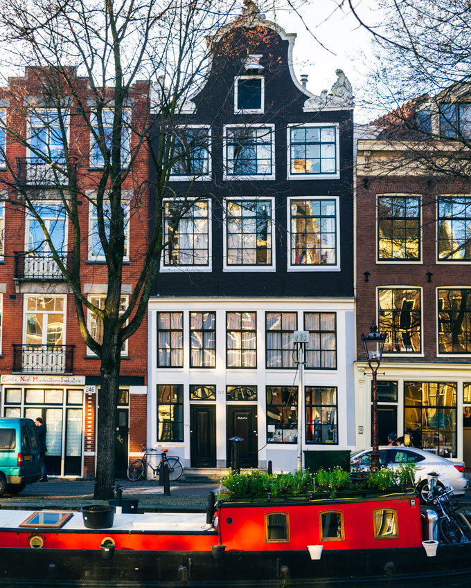 Canal houses and red houseboat in Jordaan, a popular spot for 2 days in Amsterdam