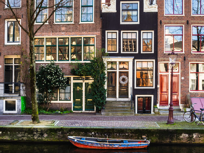 Amsterdam canal houses with blue and red rowboat