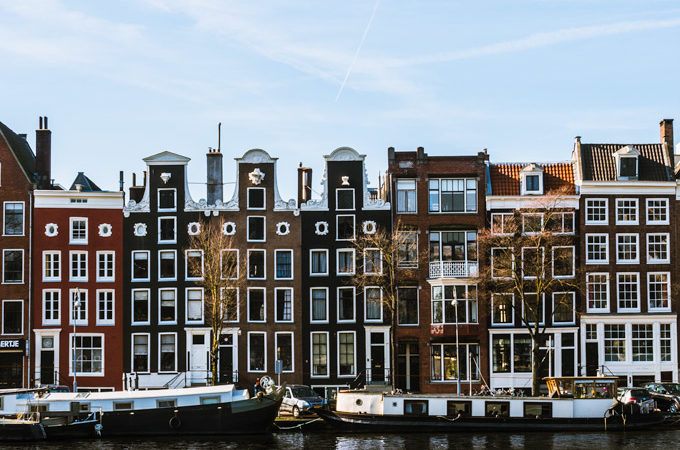 Amsterdam Damrak houses with curving tops and boats on canal, a famous Instagram worthy places in Europe