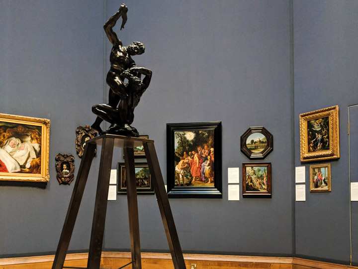 Exhibit room inside Scottish National Gallery with five oil portraits and black statue of man