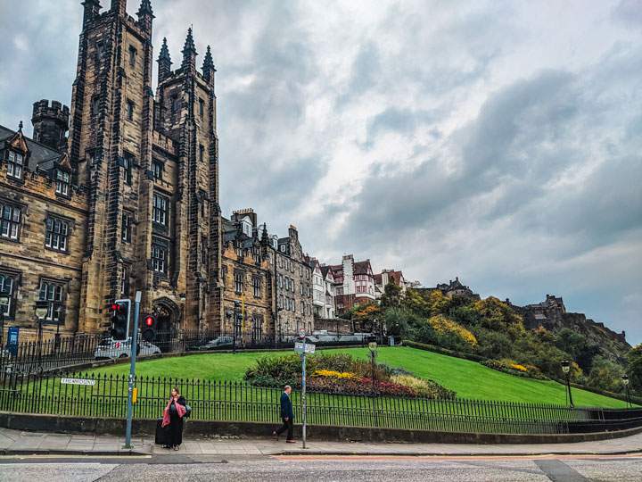 Gothic style mansion behind green lawn against dark cloudy sky in Edinburgh