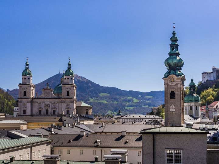 Panoramic view of Salzburg city center including cathedral spires and mountains