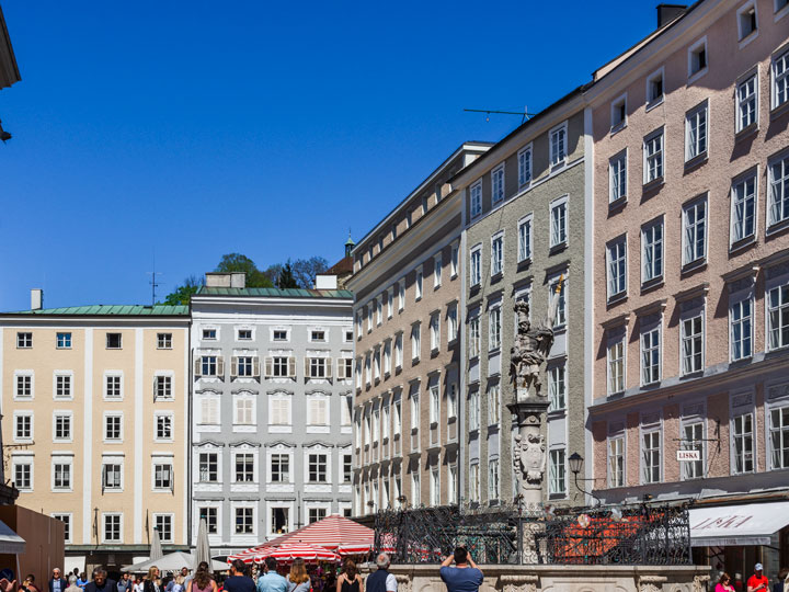 Salzburg city center with pink, white, and yellow buildings and tall water fountain