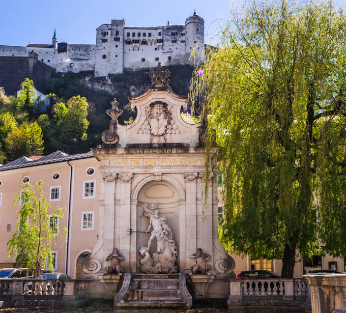 Kapitelschwemme fountain with willow tree and view of Salzburg fortress above