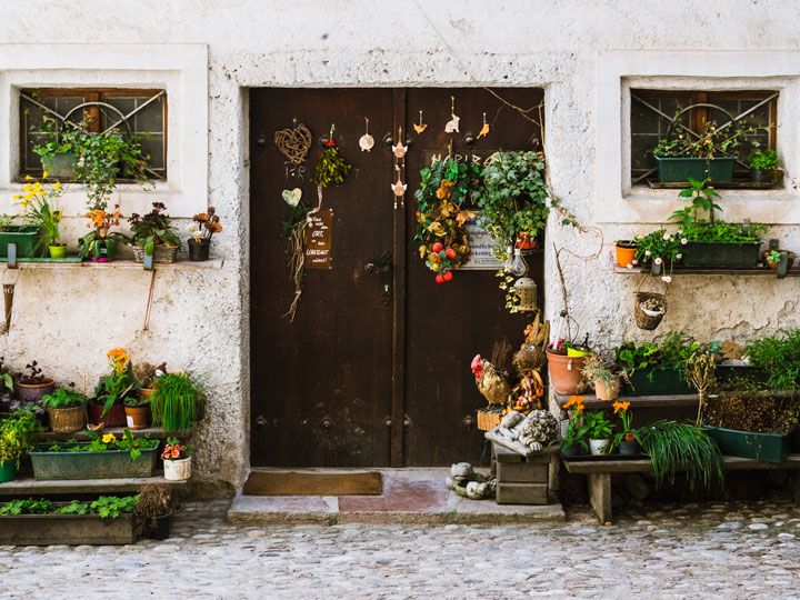 Old stone house facade with brown doors and hanging plants seen during 2 days in Salzburg itinerary