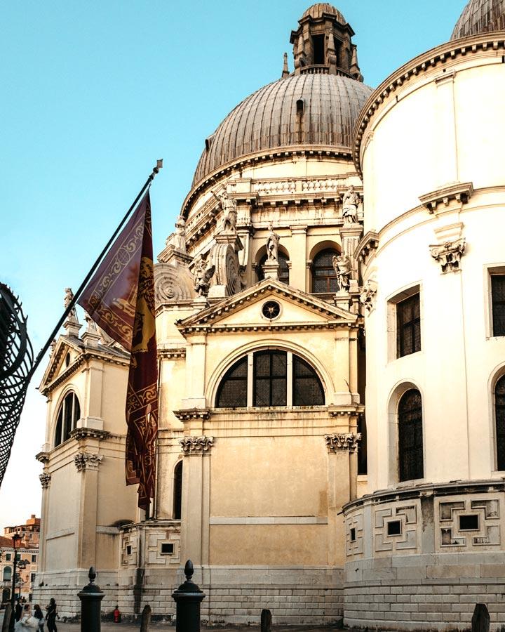 Exterior of Basilica di Santa Maria della Salute in Venice with Venetian flag