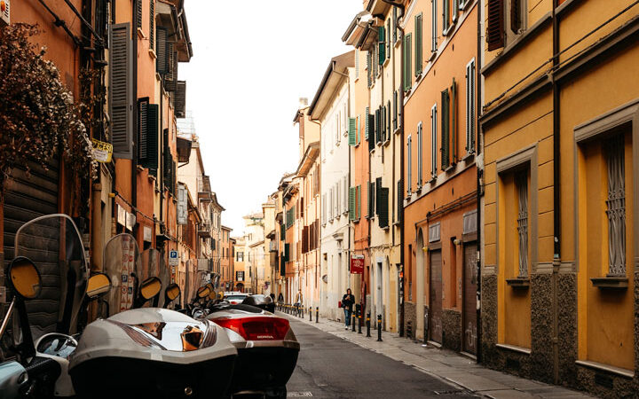 3 days in Bologna itinerary - view of alley with mopeds and yellow orange walls