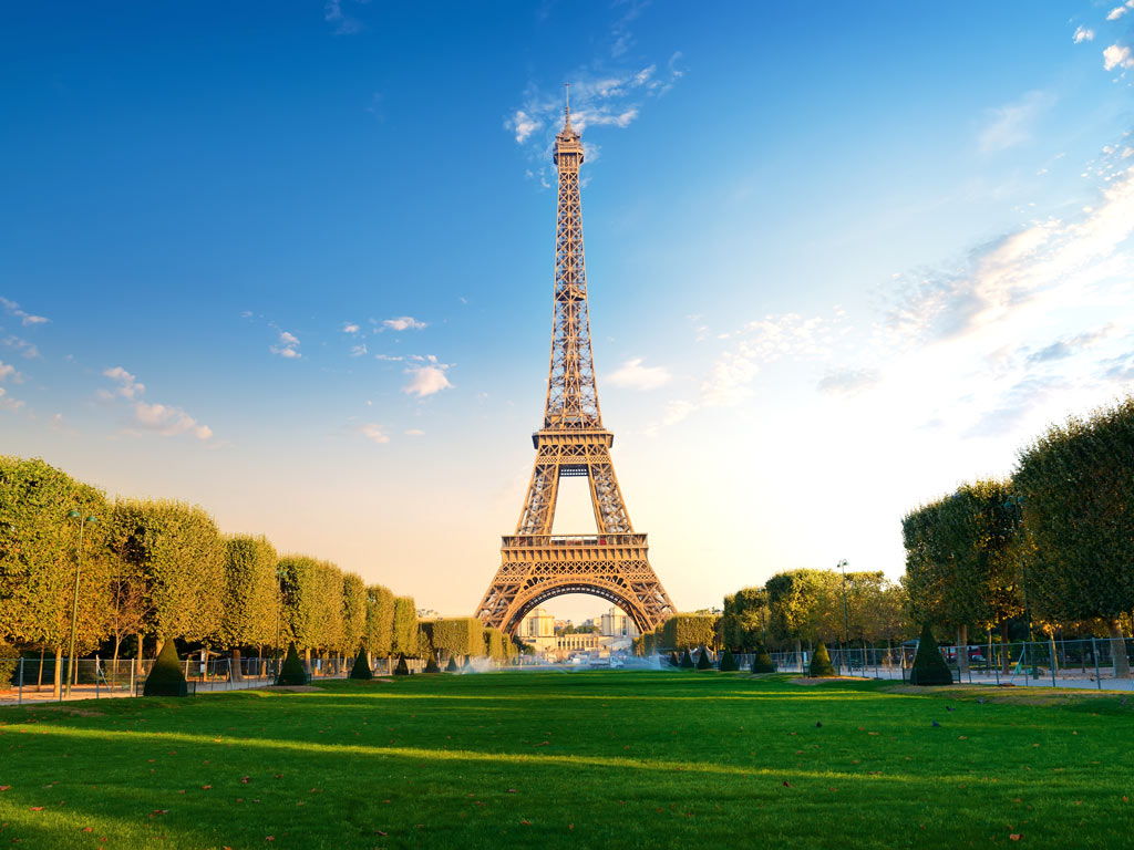 View of Eiffel Tower at sunrise from Champs de Mars park during 4 days in Paris itinerary.
