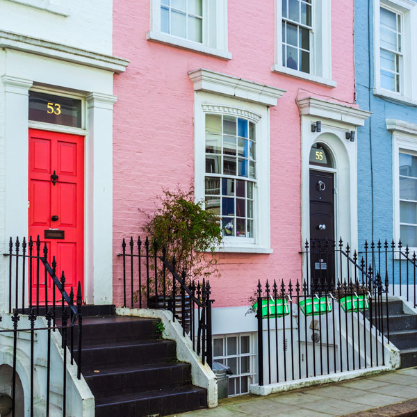 London row homes with pink and black doors and pink facade
