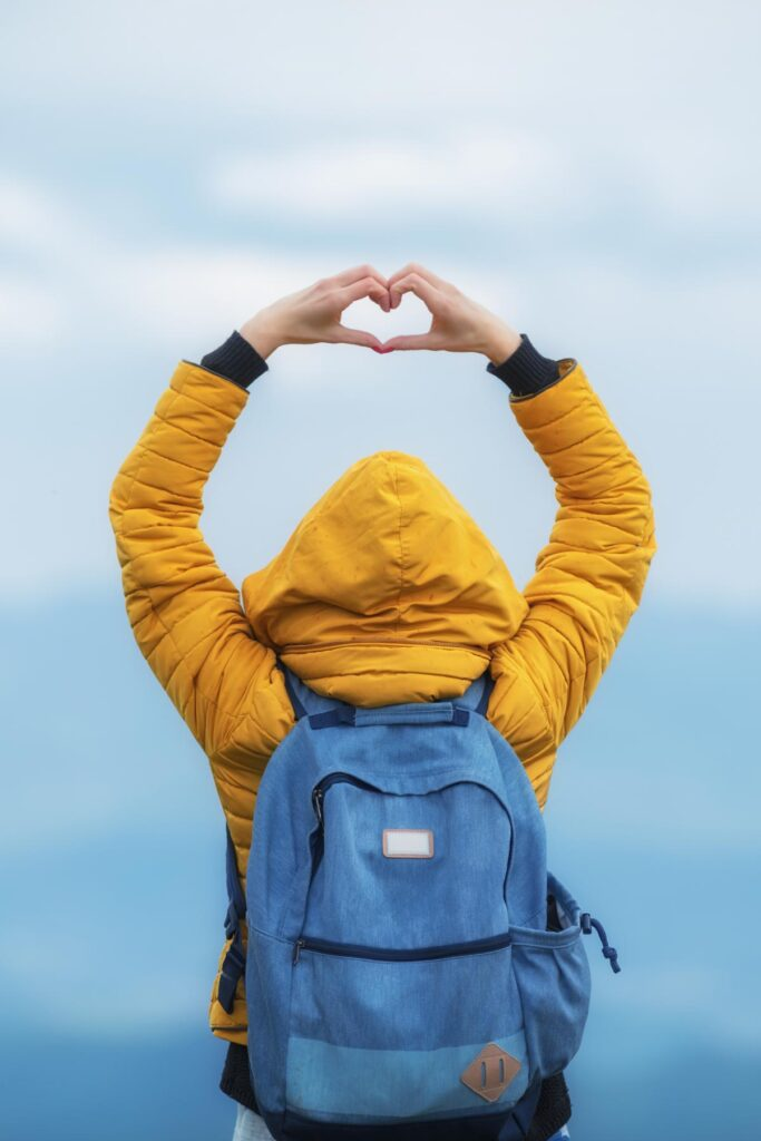 Woman in yellow jacket and blue backpack making heart shape with hands over heard.