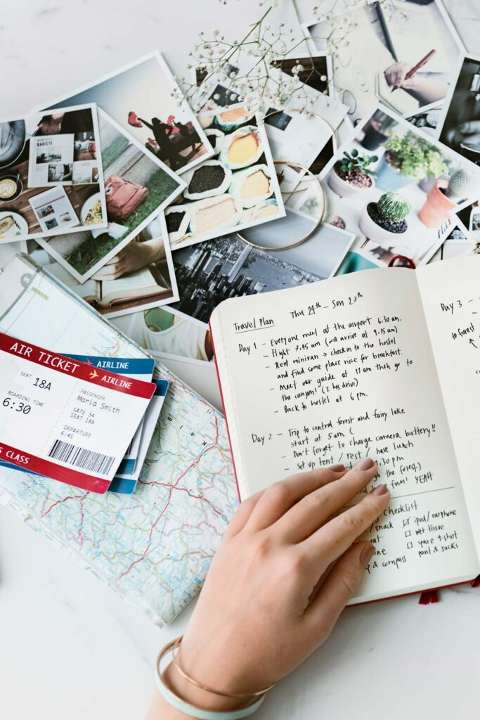Table with photos, plane tickets, and journal to record travel planning resources.