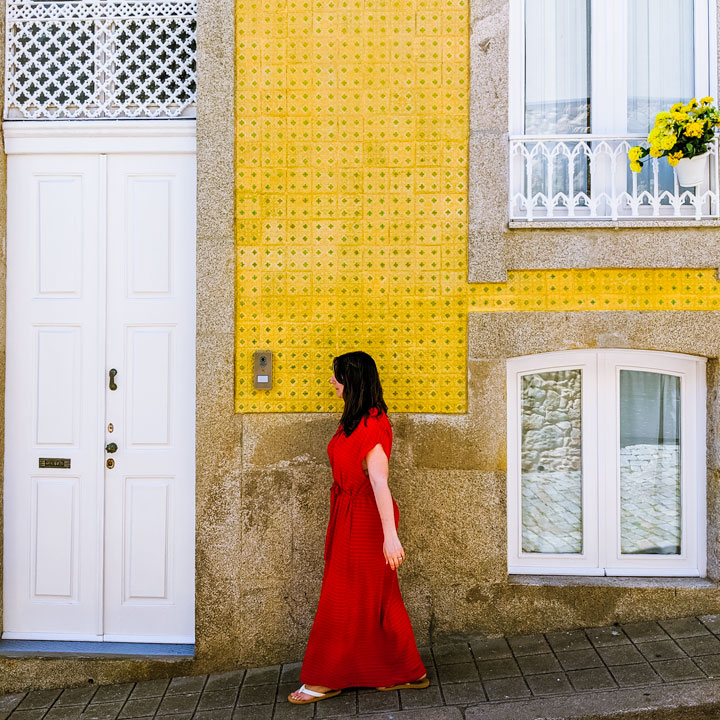 The Portable Wife wearing red dress in front of yellow wall