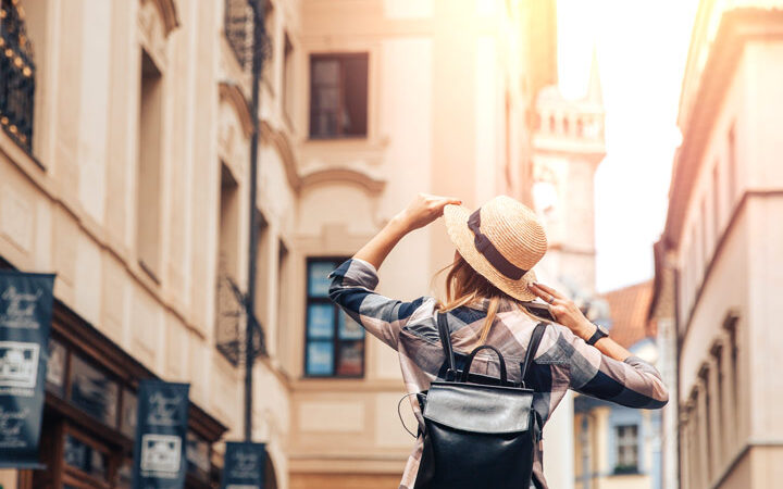 Girl holding straw hat walking down European street considering advantages of living abroad