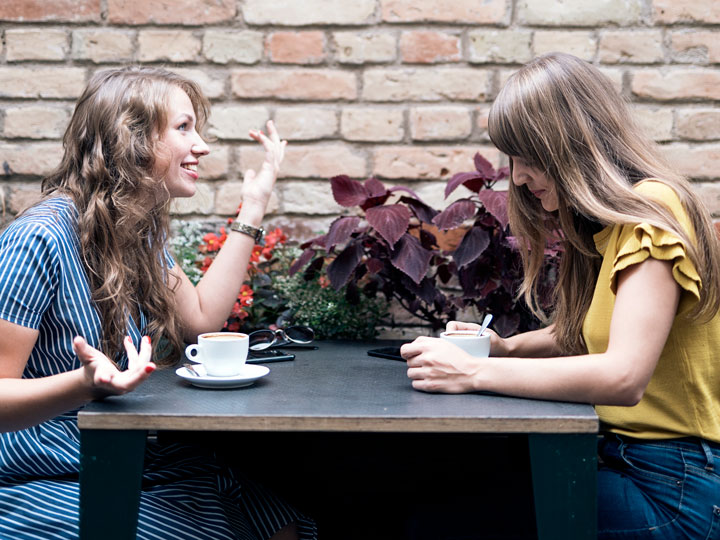 Two young women drinking coffee  at table and discussing advantages of living abroad
