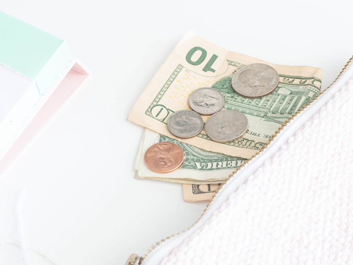 10 dollar bill and coins next to white zip wallet