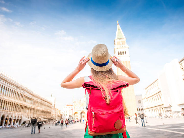 Girl with red backpack holding straw hat in Venice St. Mark's Square