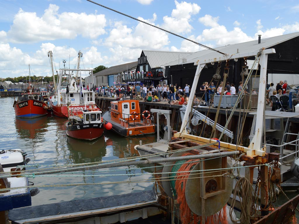 View of Whitstable dock with boats and restaurants.