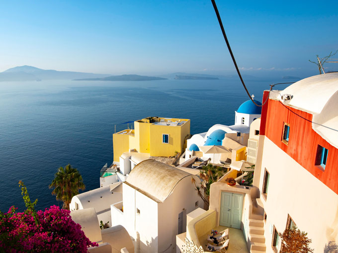 Oia white houses with blue dome and yellow details overlooking the ocean