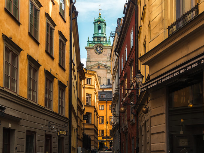 Gamla Stan clock tower viewed from alley with yellow buildings, both popular Europe Instagram spots
