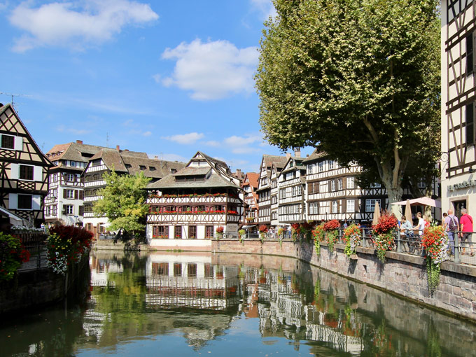 Waterfront view of Petite-France Strasbourg with timbered buildings and trees