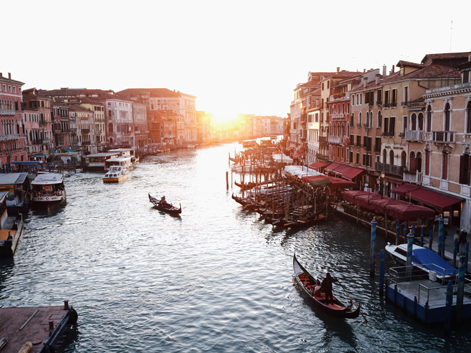 Sunset over Venice canal with two gondolas and old buildings on waterfront