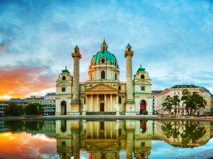Sunset at domed Vienna Karlskirche with water reflection, an iconic Europe Instagram spot