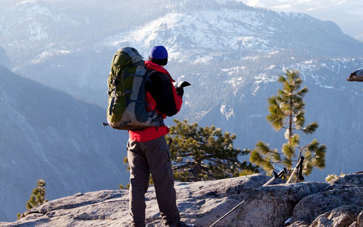 Best gifts for hikers - backpacking man standing on cliff with mountain view