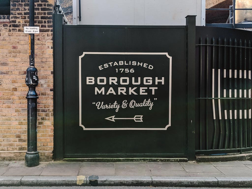 Sign outside Borough Market with arrow pointing the way left.