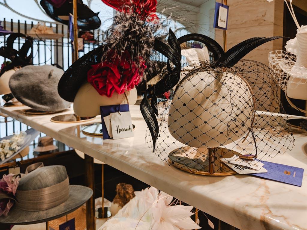 Fancy hats on display inside Harrods department store.