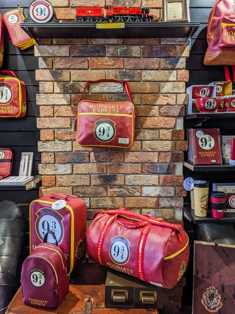 Display of Harry Potter stuff in London shop House of Spells, including duffel bags and mugs.