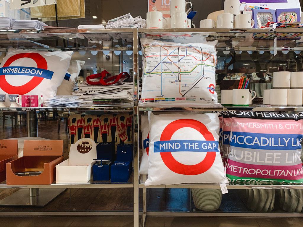 Shelves of London souvenirs including pillows, mugs, tote bags, etc.