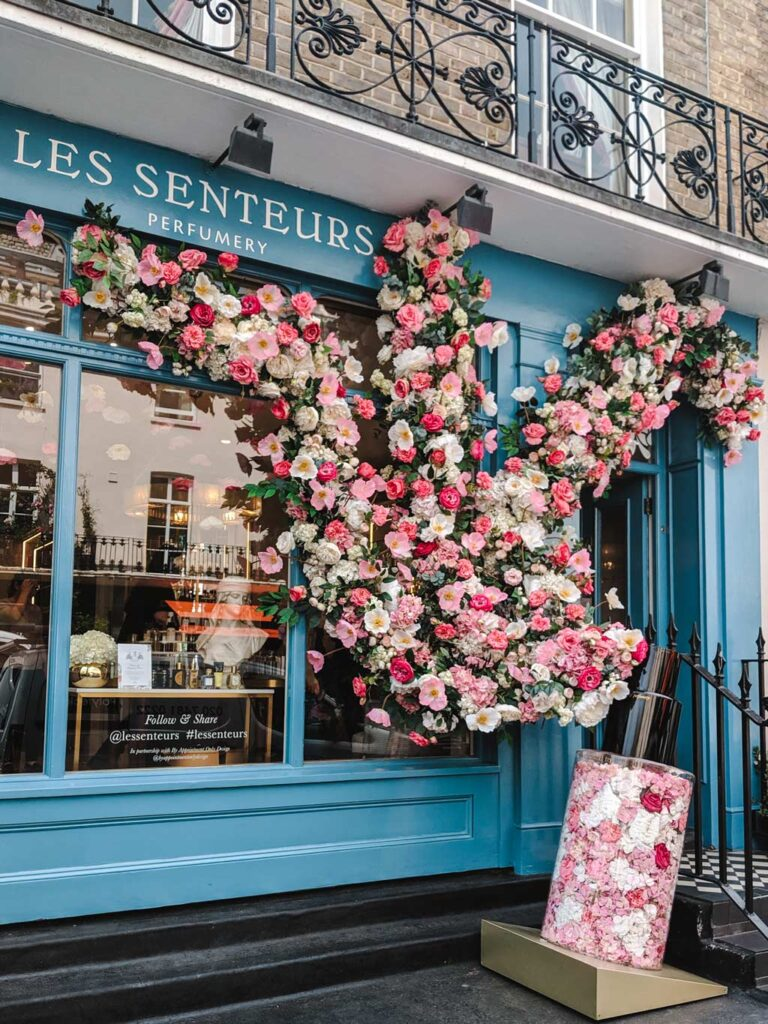 Blue facade of Les Senteurs with flowers and roses on window.