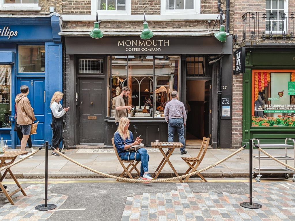 Exterior of Monmouth Coffee shop in Covent Garden with people waiting in line to enter.