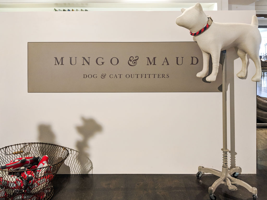 Storefront display of Mungo & Maud with white dog doll on stand.