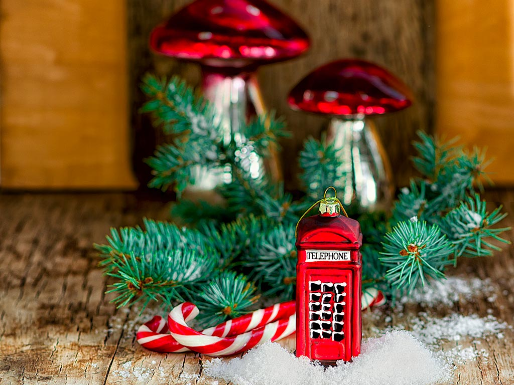 Red phone box ornament in front of pine branch on table.