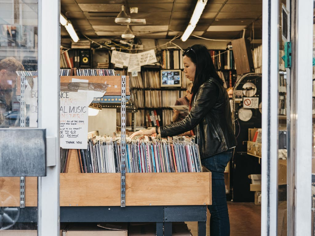 Woman shopping for gifts in London at vinyl record shop.