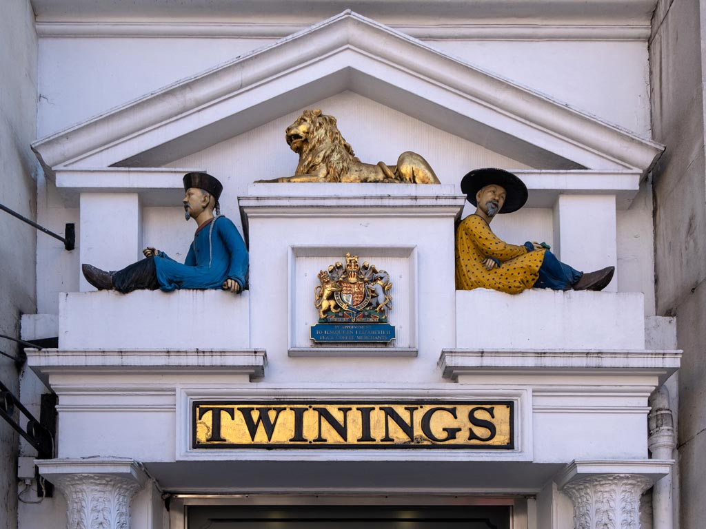Close-up of Twinings facade with statues of two men and golden lion.