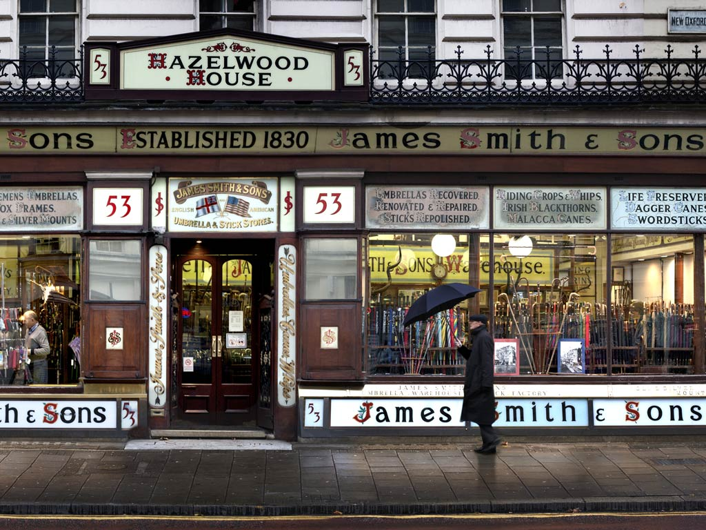 Exterior of James Smith & Sons umbrella store with man holding umbrella outside door.