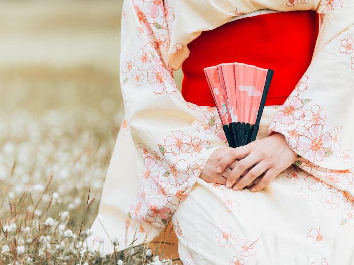 Woman in cream colored kimono sitting in field holding pink hand fan