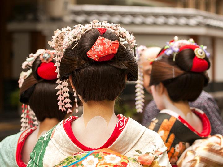 Three geisha walking away with floral hair ornaments kanzashi