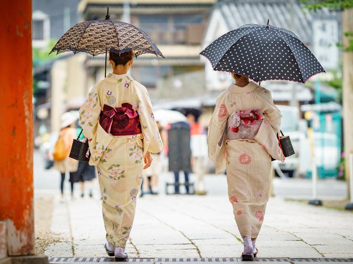 Two women wearing cream colored kimono walking with umbrellas
