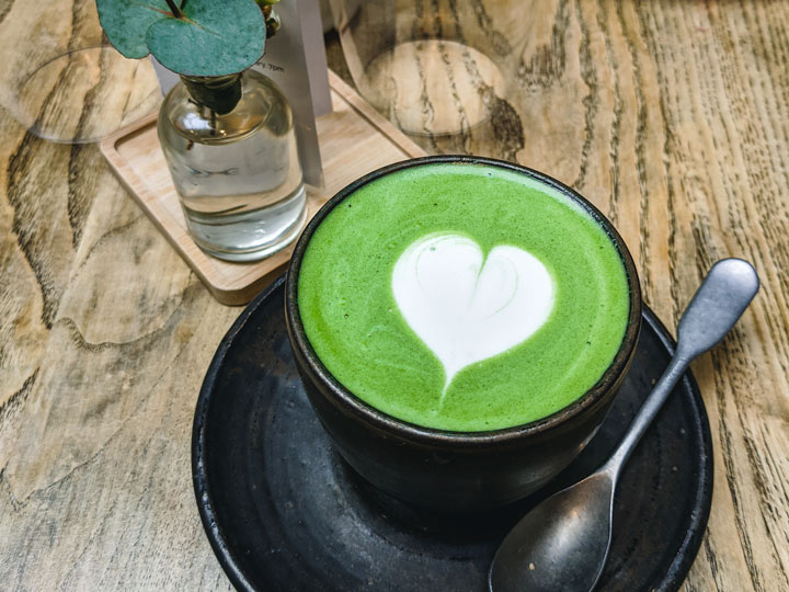 Matcha latte with white heart in black cup