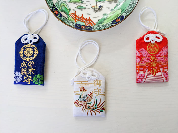 Blue, red, and white omamori Japanese souvenirs with tea saucer