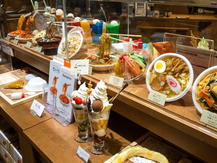 Shelf of Japanese souvenir plastic food displays (sampru), including parfait and ramen